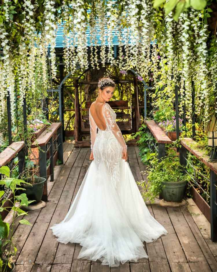 woman in white wedding gown standing on brown wooden pathway